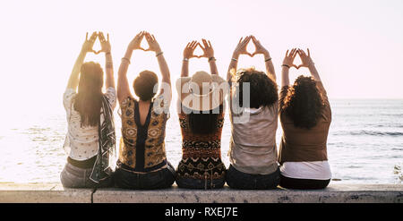 Group of young activist women viewed from rear doing feminism symbol and female power and respect with hands - sun and outdoor nature and sunset in ba - Stock Image