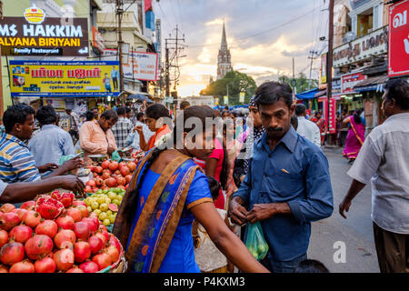 A man and a woman buy fruit with Our Lady of Lourdes Church in background, Netaji Subhas Chandra Bose Rd, Tiruchirappalli, Tamil Nadu, India. - Stock Image