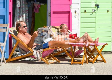 Lyme Regis, Dorset, UK.  4th July 2019. UK Weather.  A couple sunbathing outside a seafront beach hut at the seaside resort of Lyme Regis in Dorset enjoying a day of clear skies and scorching hot sunshine.   Picture Credit: Graham Hunt/Alamy Live News - Stock Image