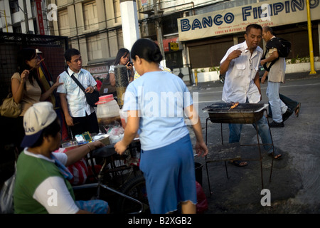 Filipinos stop for a quick snack at a street vendor's barbeque stand in Makati City, Metro Manila, Philippines. - Stock Image