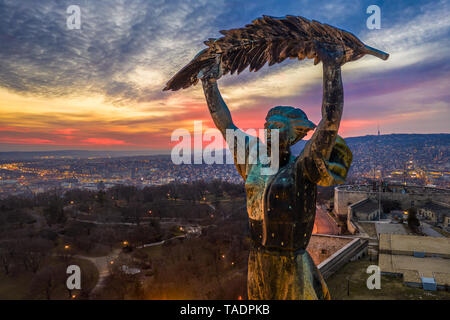 Budapest, Hungary - Aerial view of the Hungarian Statue of Liberty with amazing colorful sunset and sky behind at winter time - Stock Image