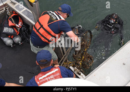 Crews from the Coast Guard Regional Dive Locker West, Maritime Security Response Team West, and Coast Guard Aids to Navigation Team San Diego lift a derelict bike found by divers at the bottom of the San Diego Bay onto the deck of ANT San Diego's Trailerable Aids to Navigation Boat Aug. 25, 2018. The crews searched the San Diego Bay along North Harbor Drive for debris as part of Operation Clean Sweep 2018. (U.S. Coast Guard photo by Petty Officer 2nd Class Joel Guzman/released) - Stock Image