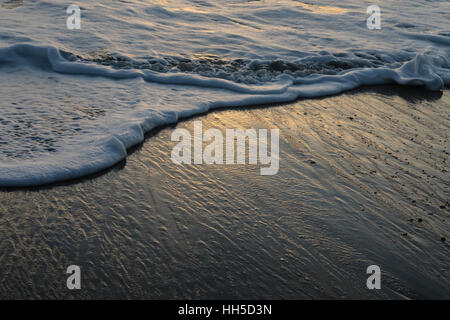 waves glittering in the evening sun - Stock Image