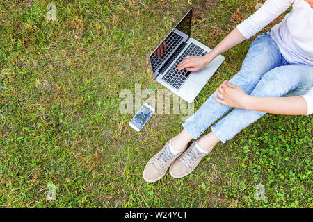 Freelance business concept. Woman legs on green grass lawn in city park, hands working on laptop pc computer. Lifestyle authentic candid student girl - Stock Image