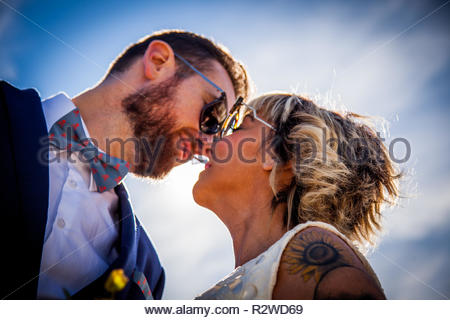 Couple of newlyweds pose together under a blue sky - Stock Image