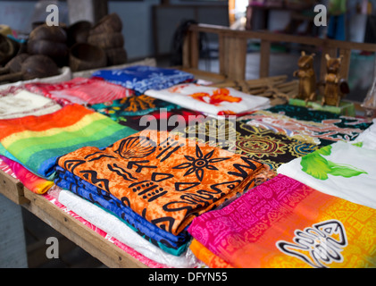 Bright and colourful clothing and materials on sale in a Thai market. - Stock Image