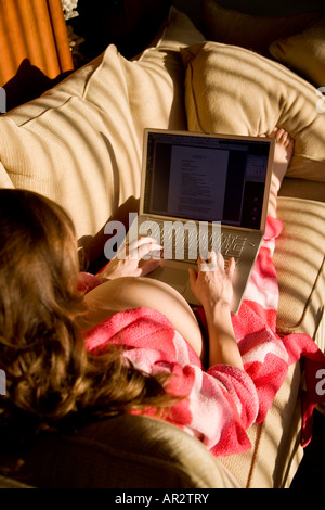 Pregnant woman relaxing in her robe on the sofa using her laptop - Stock Image