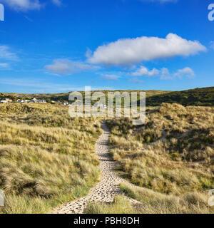 The South West Coast Path passes through sand dunes near Holywell Bay, Cornwall, UK. - Stock Image