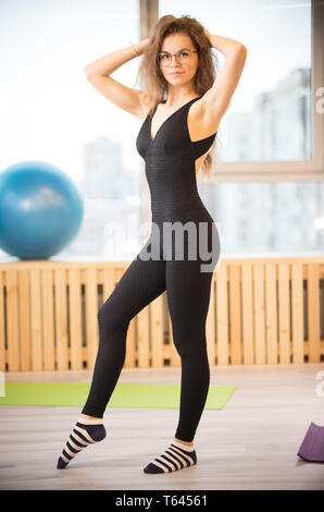 Young slim woman in glasses in the fitness studio - Stock Image