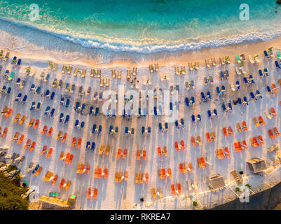 Thasos Marble Beach at sunrise with empty sunbeds and umbrellas on the white sand beach - Stock Image