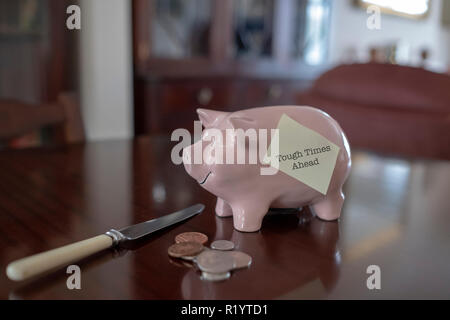 Piggy bank on polished table with loose change and knife and post it note saying tough times ahead - Stock Image