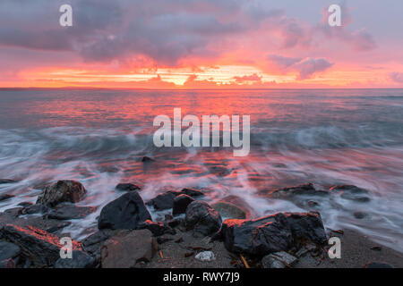 Mousehole, Cornwall, UK. 8th March 2019. UK Weather.  There was a fiery sunrise at Mousehole this morning, with a brief shower of rain before the sun came up. Credit: Simon Maycock/Alamy Live News - Stock Image