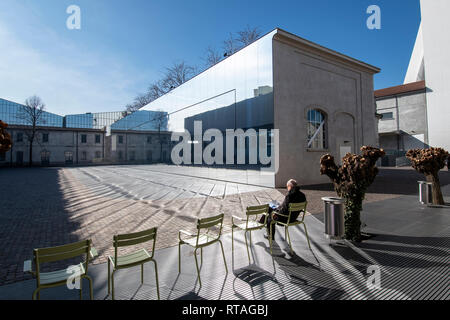 Man sitting on a chair in one of the couryards of Fondazione Prada, exterior, Milan, Italy - Stock Image