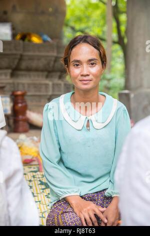 Siem Reap, Angkor, Tempel Baphuon, eine Frau die vor einer großen Buddhastatue sitzt und für Touristen gegen Geld betet - Stock Image