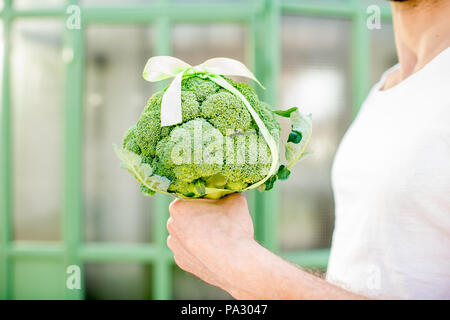Holding fresh bunch of broccoli tied in a bow as a gift outdoors on the green background - Stock Image