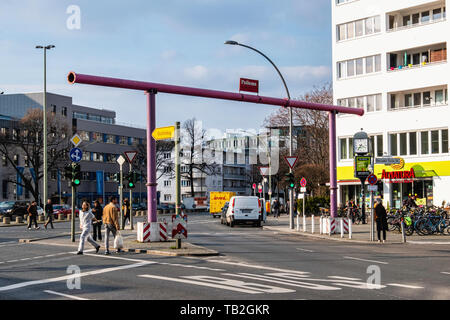 Schöneberg-Berlin. Old pink drainage pipes form an arch over street - Stock Image