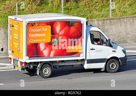 Looking down side & back view Sainsburys supermarket home food delivery van & driver with vehicle advertising fresh tomatoes driving on UK motorway - Stock Image