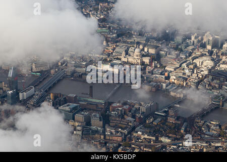 Aerial view of the Thames and St Paul's Cathedral illuminated by sunlight amidst the clouds. - Stock Image