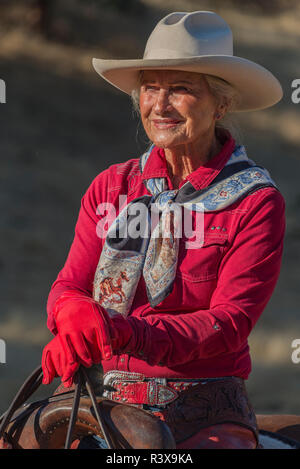 USA, California, Parkfield, V6 Ranch portrait of a cowgirl dressed in red with a hat on a horse (MR) - Stock Image