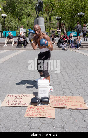 Portrait of afit muscular 53 year old man shadow boxes and solicits donations for taking photos. In Union Square Park in Manhattan, New York City. - Stock Image