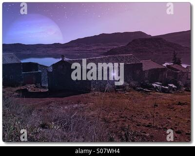 Rustic stone farmhouse beside a lake on a moonlit night. - Stock Image
