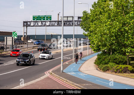 London, England, UK - June 1, 2019: Cyclists ride along the CS3 cycleway alongside traffic on the A13 East India Dock Road in London's Docklands distr - Stock Image