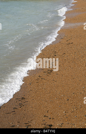Waves Gently Lapping on a Shingle and Sand Beach, Saltdean, Sussex, UK - Stock Image