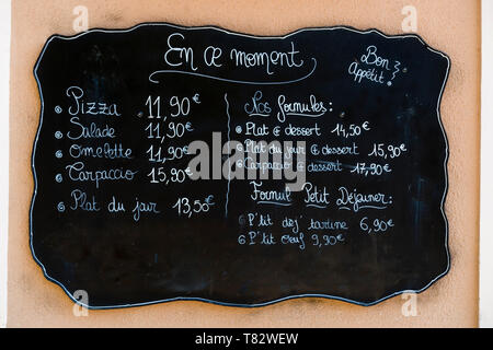 Blackboard handwritten menu outside a french restaurant with prices in euros - Stock Image