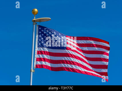 American flag blowing in the wind with blue sky background, Castle Rock Colorado US. Photo taken in April. - Stock Image