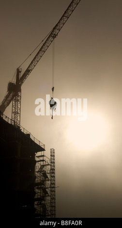 Unnidentifiable Construction site Silhouetted against the sun. Crane lifting equipment. - Stock Image