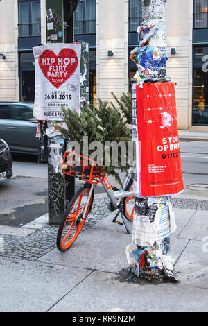 Berlin, Mitte,A Christmas tree dumped in the basket of a orange Mo Bike rental Bicycle parked on a pavement - Stock Image