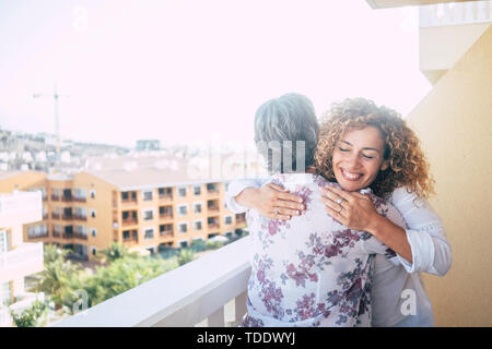 Love for friends or family concept with curly beautiful happy middle age woman hugging a mature grey hair senior lady on the terrace at home with city - Stock Image