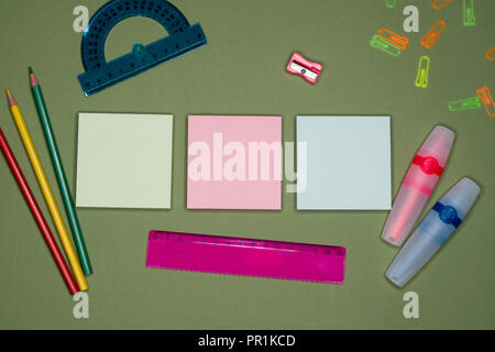 School concept. Empty adhesive notes, stationery on green background, blank copy space. - Stock Image