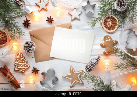 Christmas lights,fir branch,cookies and letter on wooden background - Stock Image
