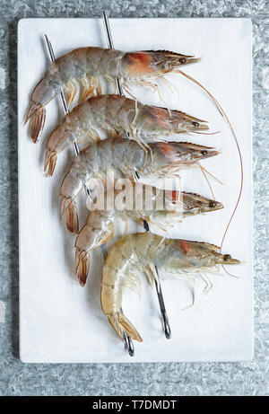 Five Raw Whole Prawns on Skewers - Stock Image