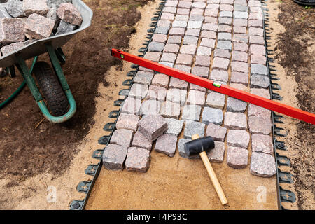 landscaping and garden services - granite cobblestone walkway construction - Stock Image