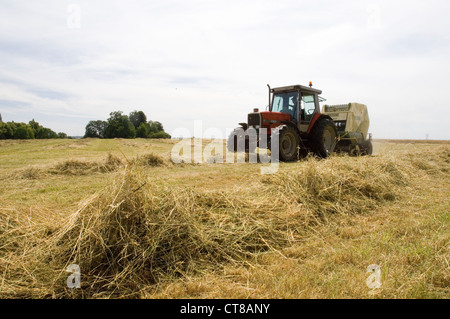 Tractor during hay making in Oxfordshire field. - Stock Image