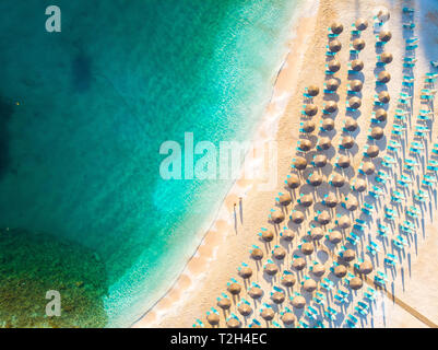 Beach with sun chairs and umbrellas top down aerial view - Stock Image