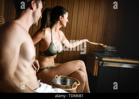 Beautiful couple relaxing in sauna and caring about health and skin - Stock Image