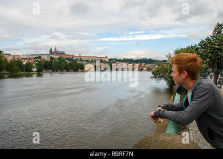 The tourist leaned on the fence of the Vltava river and admires the views of old Prague - Stock Image