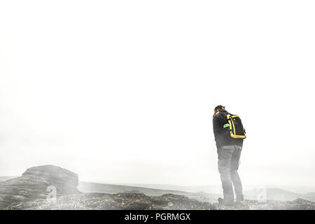 A man hikes through the fog in Dartmoor National Park - Stock Image