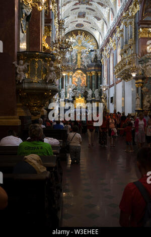 The interior of the basilica in the Sanctuary of Jasna Góra is crowded with pilgrims who celebrate the assumption of Mary, Poland 2018. - Stock Image