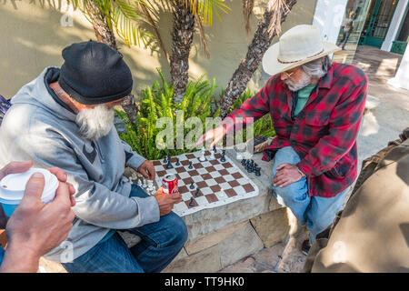 An older Caucasian male holds a sign challenging people to a game of chess. He has his chess board set up ready to play on a low stone wall. - Stock Image