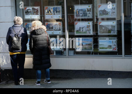 Two women looking in an estate agents window in Falmouth, Cornwall. - Stock Image