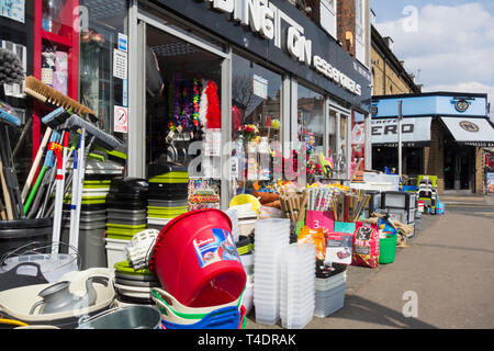 Multicoloured plastic items outside an ironmongers store in London, UK - Stock Image