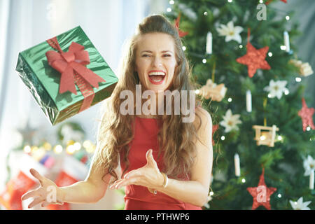 smiling stylish woman in red dress near Christmas tree throwing up green Christmas present box - Stock Image