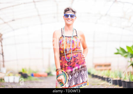 Cheerful happy young blonde woman smile and pose for hippy clothes portrait - happiness and colorful lifestyle for alternative people outdoor - trendy - Stock Image