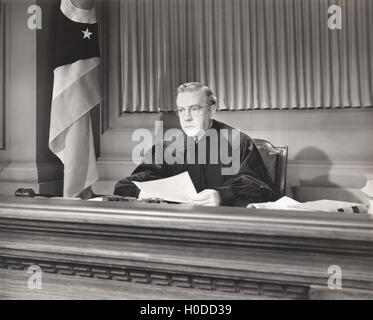 Judge holding a document in courtroom - Stock Image