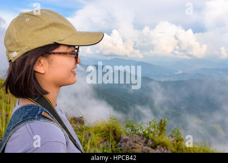 Hiker asian cute teens girl with caps and glasses smiling happily while looking beautiful landscape nature of mountain - Stock Image