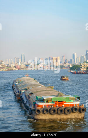 River transport in South East Asia: a cargo barge passes down the Chao Phraya River in Bangkok, Thailand, carriying - Stock Image